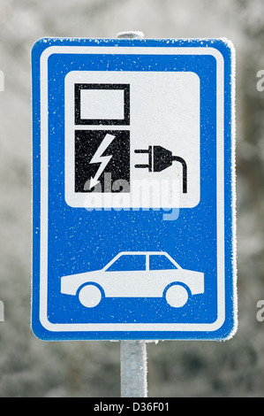 Electric vehicle charging station sign at car park in the snow in winter, Belgium - Stock Photo