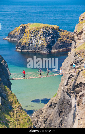 Tourists crossing the Carrick a rede rope bridge to Carrick island Ballycastle County Antrim Northern Ireland UK - Stock Photo