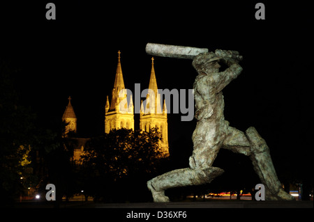 Sir Donald Bradman statue in Adelaide, South Australia at night with St Peters cathedral in the background - Stock Photo