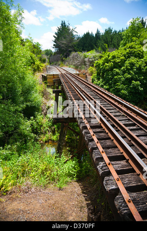 A view along a working railway track on an old trestle bridge over a river. Northland, North Island, New Zealand. - Stock Photo