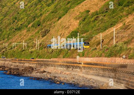 The Metlink Kapiti line train on the Kapiti coast highway between pukerua Bay and Paekakariki. - Stock Photo