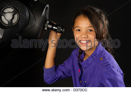 young girl about to look through a telescope. she is looking at the camera. - Stock Photo