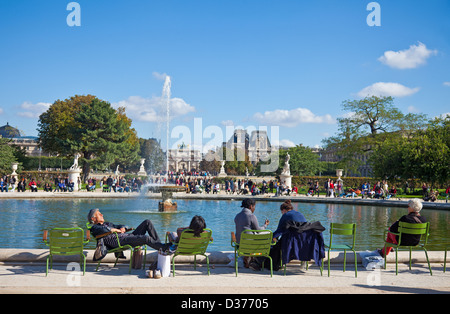 People enjoying some autumn sunshine around the edge of a pond: Jardin des Tuileries, Paris. Louvre museum in background. - Stock Photo