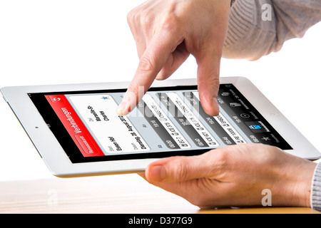 Person is using a tablet computer. Train time table. - Stock Photo