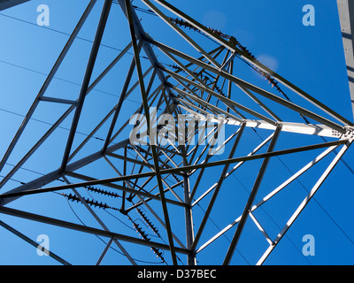 A electricity pylon against a blue sky, shot from underneath - Stock Photo