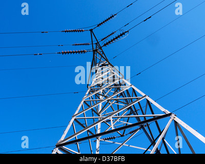 A electricity pylon against a blue sky - Stock Photo