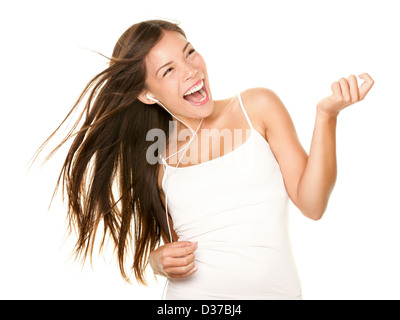 Happy young Asian / Caucasian woman listening to mp3 player with earphones while playing air guitar isolated on - Stock Photo