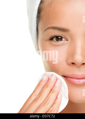 Closeup portrait of pretty beautiful mixed race woman removing face makeup with cotton swab pad isolated on white - Stock Photo
