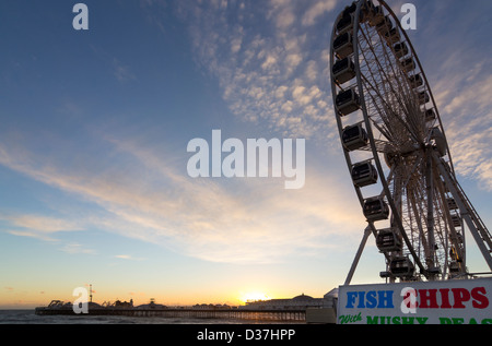 Brighton Wheel and Brighton Pier on a winter evening with the sun setting - Stock Photo