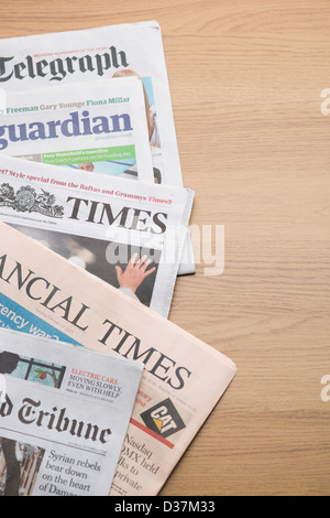 Selection of broadsheet quality newspapers from the United Kingdom laid out on a wooden tabletop. - Stock Photo