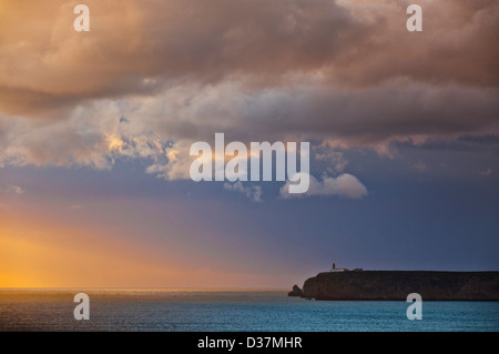 Stormy sunset over Atlantic ocean and cliffs at Cape St. Vincent with lighthouse in the distance Sagres Algarve - Stock Photo