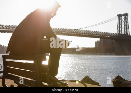 Man using cell phone by urban bridge - Stock Photo