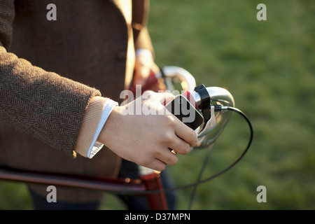 Man with cell phone pushing bicycle - Stock Photo