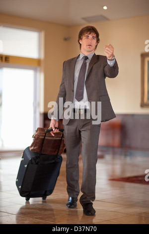 Businessman rolling luggage in lobby - Stock Photo