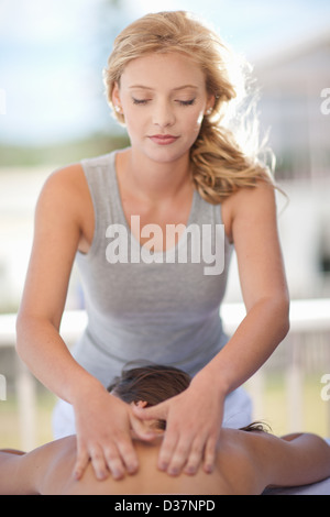 Woman giving massage outdoors - Stock Photo