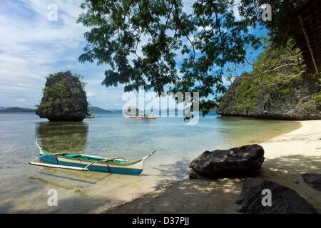 Sandy beach with outrigger boats off the island of Coron, nature reserve Balnek, Coron, Palawan, Philippinen, Asia. - Stock Photo
