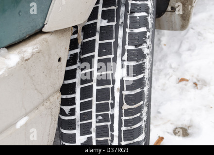 closeup of car tire tread protector full of snow in winter. - Stock Photo