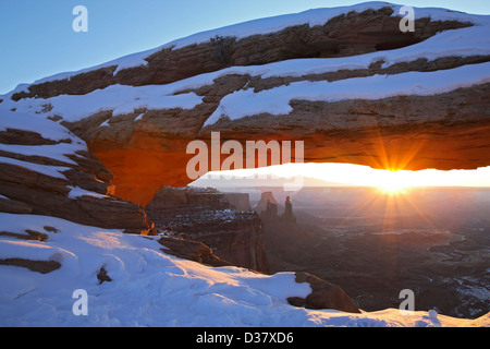 Mesa Arch covered in snow and sunburst, Island in the Sky District, Canyonlands National Park, Utah USA - Stock Photo
