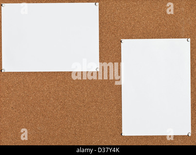 two blank white sheets of paper on cork board stock photo