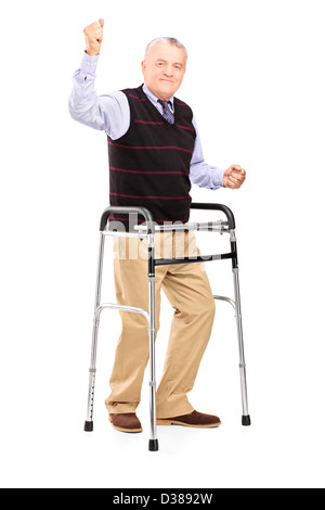Full length portrait of a happy mature gentleman with walker gesturing happiness isolated on white background - Stock Photo
