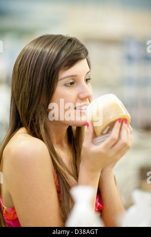Woman smelling candle in store - Stock Photo