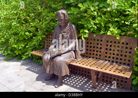 Bronze statue of a woman sitting on a bench in the Triunfo Garden in Granada, Andalucia, Spain - Stock Photo