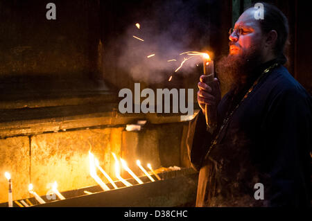 Jerusalem, Israel. 13th February 2013. A priest blows out a candle by the Edicule of the Tomb as thousands of Christian - Stock Photo