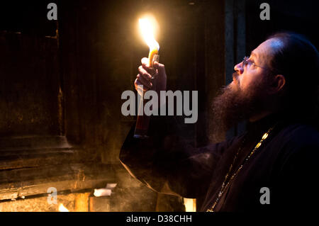 Jerusalem, Israel. 13th February 2013. A priest holds a candle and looks up at the Edicule of the Tomb in the Church - Stock Photo