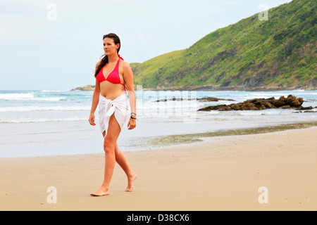 A young woman walks on a remote South African beach in the late afternoon - Stock Photo