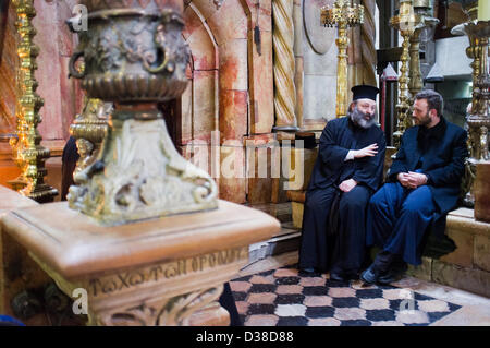 Jerusalem, Israel. 13th February 2013. Two priests converse at the entrance to what is believed to be the tomb of - Stock Photo
