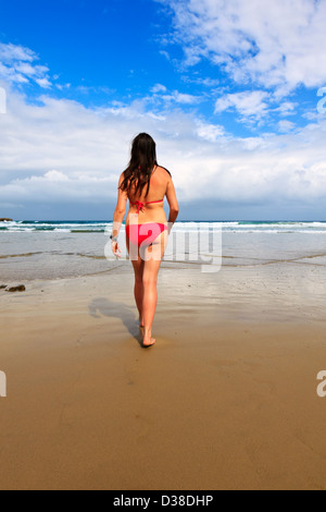 A young woman on a remote beach going for a swim in the late afternoon sun. - Stock Photo