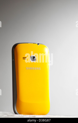A yellow Samsung mobile phone. - Stock Photo