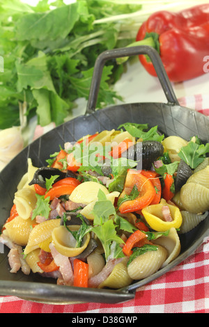 colorful Pasta pan with bell pepper, turnip greens, ham strips, tomatoes and garlic - Stock Photo