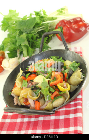 Pasta pan with bell pepper, turnip greens, ham strips, tomatoes and garlic - Stock Photo