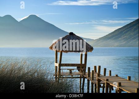 Wooden pier in still lake - Stock Photo