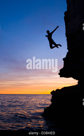 Silhouette of man cliff diving - Stock Photo