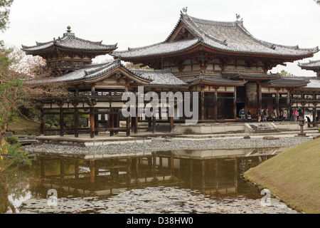 Tourists visiting Japanese garden with pond and waterfall ...