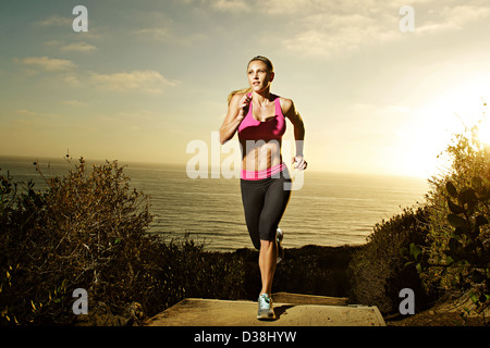 Woman running on staircase - Stock Photo