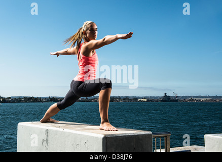 Woman practicing yoga on concrete block - Stock Photo