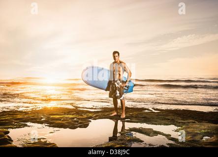 Man carrying surfboard on rocky beach - Stock Photo