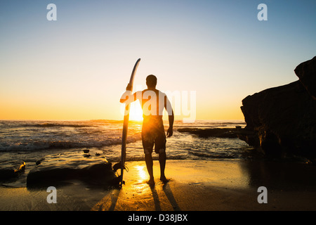 Man holding surfboard on rocky beach - Stock Photo