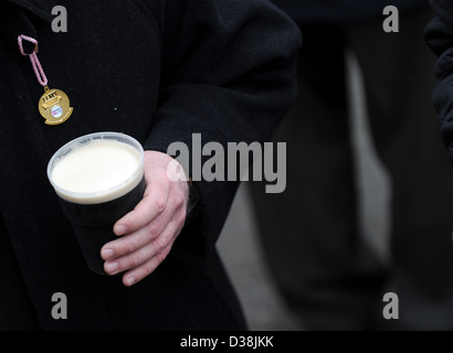A man drinks a pint of Guinness on St. Patricks Day during the Cheltenham horse racing festival - Stock Photo