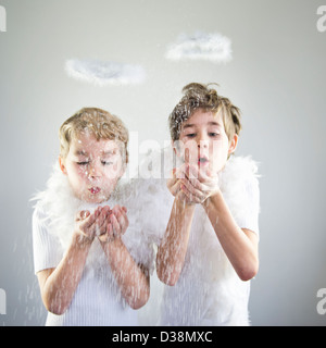 Boys with halos catching snow indoors - Stock Photo