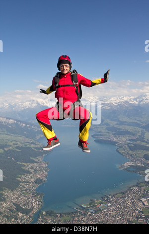Woman skydiving over rural landscape - Stock Photo