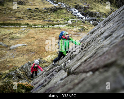 Hikers scaling steep rock face - Stock Photo