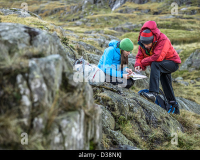 Hikers using map and compass - Stock Photo