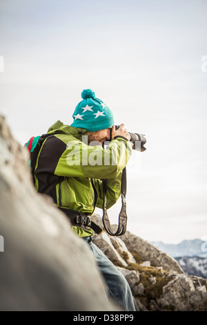 Hiker taking pictures in rural landscape - Stock Photo