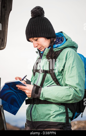 Hiker taking notes in rural landscape - Stock Photo