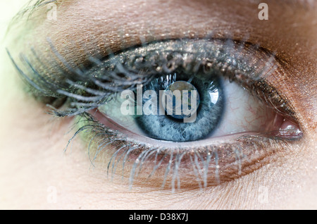 Blue Eye of Woman with Planet Earth reflection, parts of this image furnished by NASA - Stock Photo