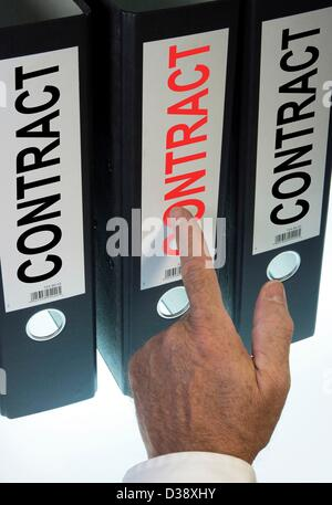 Symbol image,hand pointing to a file folder  labeled Contract - Stock Photo